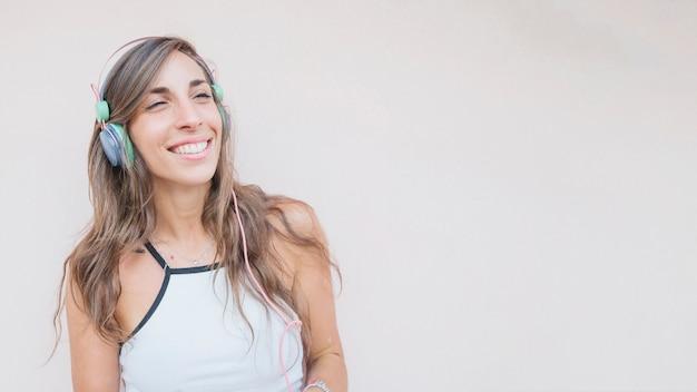 Uśmiechniętej młodej kobiety słuchająca muzyka na hełmofonie przeciw barwionemu tłu