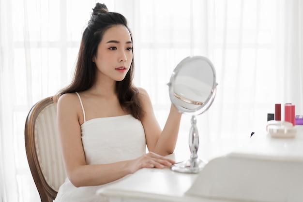 Uśmiechniętej młodej pięknej asiann kobiety świeża zdrowa skóra patrzeje na lustrze z makeup kosmetykami ustawiającymi w domu twarzowy piękna i kosmetyka pojęcie