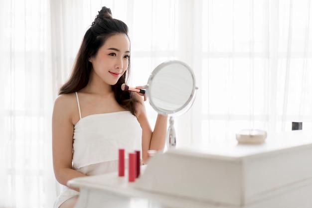 Uśmiechniętej młodej pięknej azjatykciej kobiety świeża zdrowa skóra patrzeje na lustrze