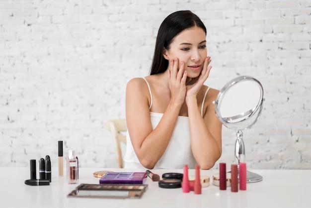 Uśmiechniętej młodej pięknej kobiety świeża zdrowa skóra patrzeje na lustrze z makeup kosmetykami ustawiającymi w domu twarzowy piękna i kosmetyka pojęcie
