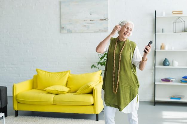 Uśmiechniętej starszej kobiety słuchająca muzyka na hełmofonie przez telefonu komórkowego