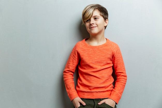 Uśmiechnięty 9-letni chłopiec z modną fryzurą w pomarańczowym swetrze spogląda na bok