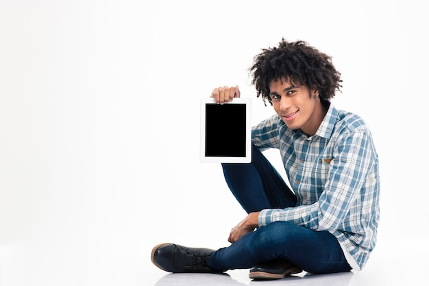 Uśmiechnięty afro amerykański mężczyzna siedzący na podłodze i pokazujący pusty ekran komputera typu tablet na białym tle na białej ścianie