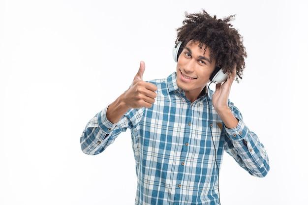 Uśmiechnięty afroamerykanin słuchający muzyki w słuchawkach i pokazujący kciuk na białym tle na białej ścianie