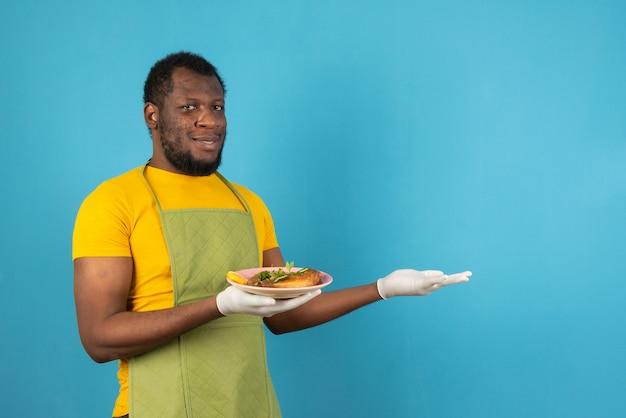 Uśmiechnięty afroamerykanin, trzymający posiłek w jednej ręce, stoi nad niebieską ścianą.