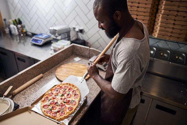 Uśmiechnięty afroamerykanin w fartuchu używający metalowej skórki podczas wkładania pysznej świeżo upieczonej pizzy do kartonowego pudełka