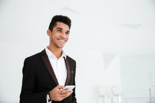 Uśmiechnięty afrykański biznesmen w czarnym garniturze, trzymający telefon w ręku, stojący w biurze i patrzący na bok