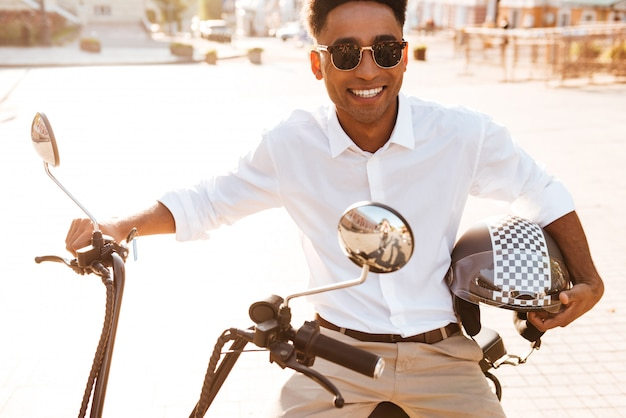 Uśmiechnięty afrykański mężczyzna siedzi na nowożytnym motocyklu outdoors i patrzeje kamerę