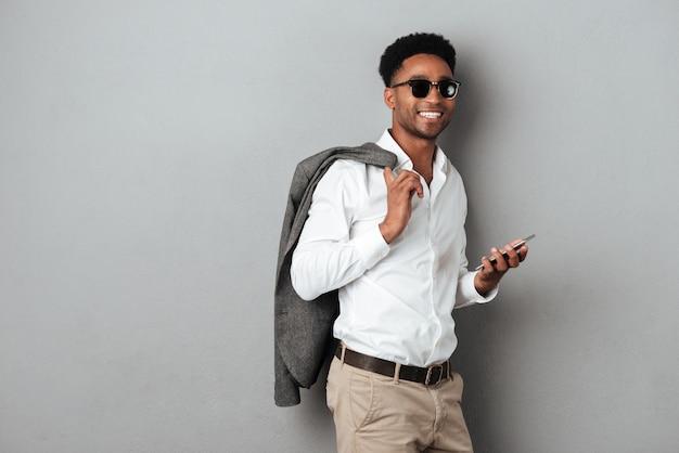 Uśmiechnięty afrykański mężczyzna trzyma kurtkę nad ramieniem w okularach przeciwsłonecznych