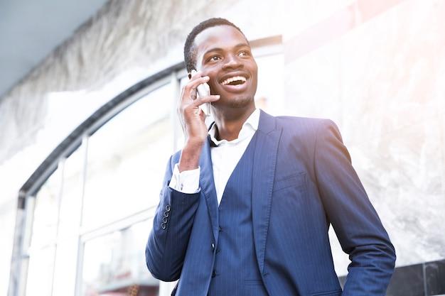 Uśmiechnięty afrykański młody biznesmen opowiada na telefonie komórkowym