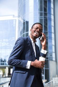 Uśmiechnięty afrykański młody biznesmen przed korporacyjnym budynkiem opowiada na telefonie komórkowym