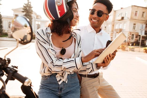 Uśmiechnięty afrykański pary obsiadanie na nowożytnym motocyklu i używać pastylka komputer na ulicie podczas gdy patrzejący each inny