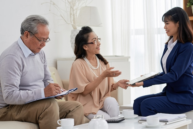 Uśmiechnięty agent nieruchomości proszący parę starszych o podpisanie dokumentów po spotkaniu