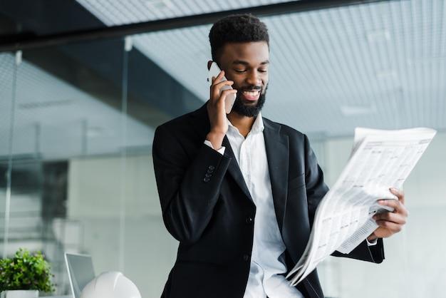 Uśmiechnięty amerykanina afrykańskiego pochodzenia biznesmen opowiada na telefonie z gazetą i filiżanką kawy w biurze