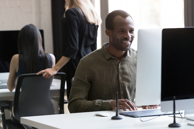 Uśmiechnięty amerykanina afrykańskiego pochodzenia biznesmen pracuje na jego komputerze