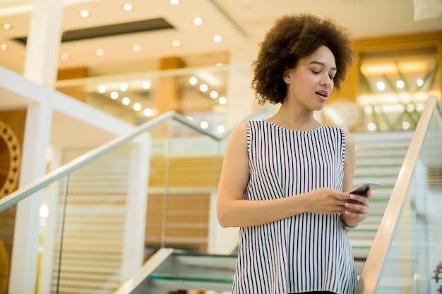 Uśmiechnięty amerykanina afrykańskiego pochodzenia bizneswoman używa telefon komórkowego w biurze
