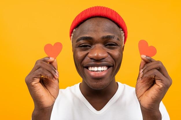 Uśmiechnięty amerykański ciemnoskóry mężczyzna w białej koszulce trzyma dwa małe kartki w kształcie serca na walentynki