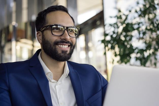 Uśmiechnięty arabski biznesmen na sobie stylowe okulary, siedząc w biurze