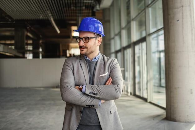 Uśmiechnięty architekt stojący w budynku w procesie budowy z rękami skrzyżowanymi