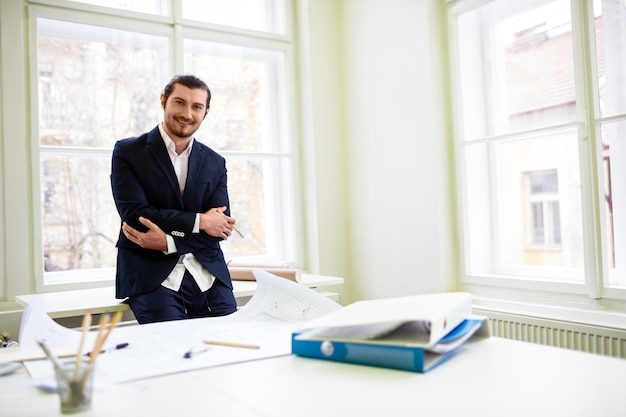 Uśmiechnięty architekt z rękami skrzyżowanymi