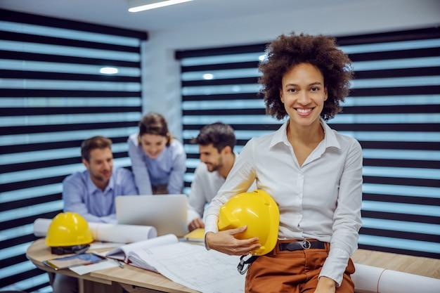 Uśmiechnięty architekt żeński rasy mieszanej siedzi na biurku w biurze i trzymając kask w dłoniach