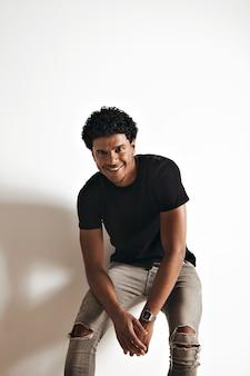 Uśmiechnięty atletyczny młody człowiek african american w pustej czarnej bawełnianej koszulce i dżinsach siedzi na białej ścianie