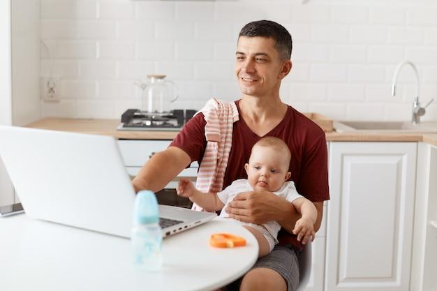 Uśmiechnięty atrakcyjny brunetka mężczyzna freelancer ubrany w bordową koszulkę w stylu casual, pracujący online i opiekujący się swoją małą córeczką, używający laptopa do pracy.