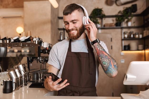 Uśmiechnięty atrakcyjny mężczyzna barista stojący za ladą w kawiarni, słuchający muzyki przez słuchawki
