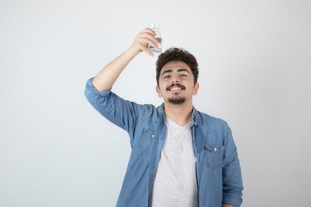 Uśmiechnięty atrakcyjny mężczyzna stojący i trzymający szklany słoik.