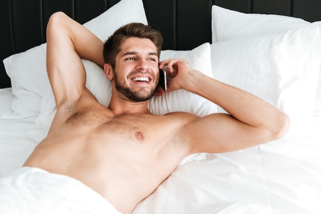 Uśmiechnięty atrakcyjny młody człowiek leży i rozmawia przez telefon komórkowy w łóżku