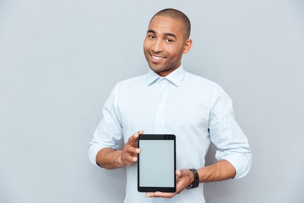 Uśmiechnięty atrakcyjny młody człowiek z afryki, trzymający tablet z pustym ekranem