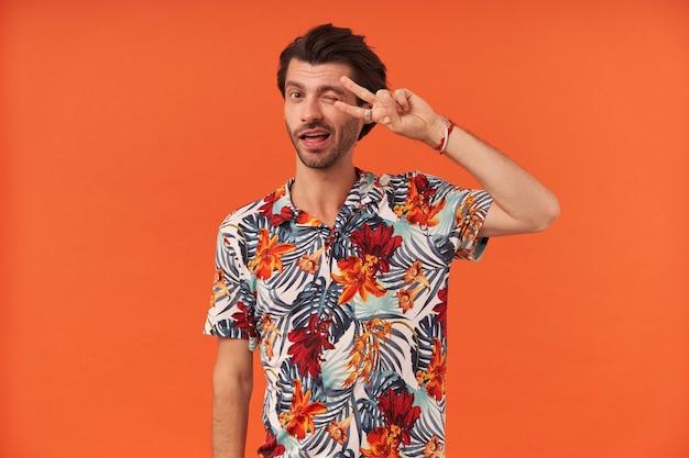 Uśmiechnięty atrakcyjny młody człowiek z włosia w kolorowej koszuli, mrugający i pokazujący znak zwycięstwa
