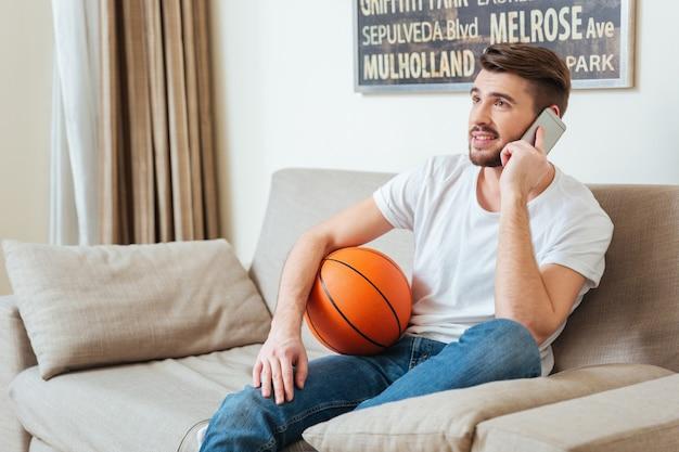 Uśmiechnięty atrakcyjny młody mężczyzna trzyma piłkę do koszykówki i rozmawia przez telefon komórkowy w domu