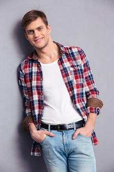 Uśmiechnięty atrakcyjny młody mężczyzna w kraciastej koszuli i dżinsach pozuje na szarej ścianie
