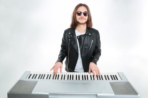Uśmiechnięty atrakcyjny młody mężczyzna z długimi włosami w okularach przeciwsłonecznych, grający na syntezatorze na białym tle