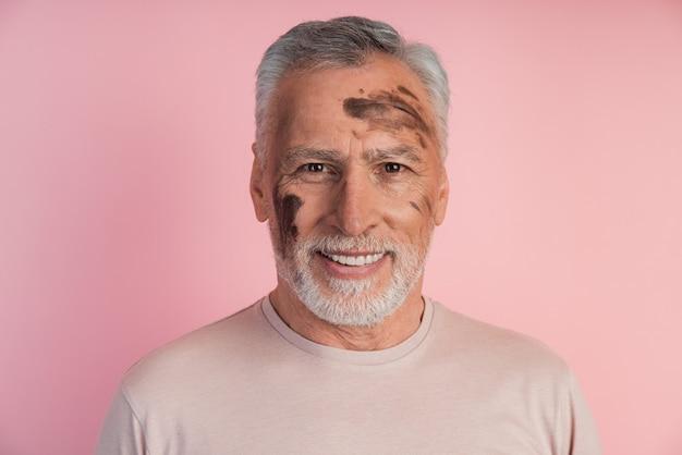 Uśmiechnięty, atrakcyjny pracownik z tłustą twarzą na ścianie różowej ściany