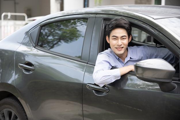 Uśmiechnięty azjatycki biznesmen prowadzący samochód i patrzący przez okno