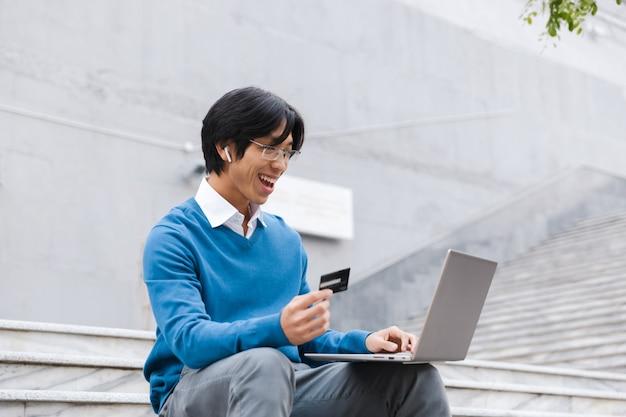Uśmiechnięty azjatycki biznesowy mężczyzna za pomocą laptopa na zewnątrz, pokazując kartę kredytową