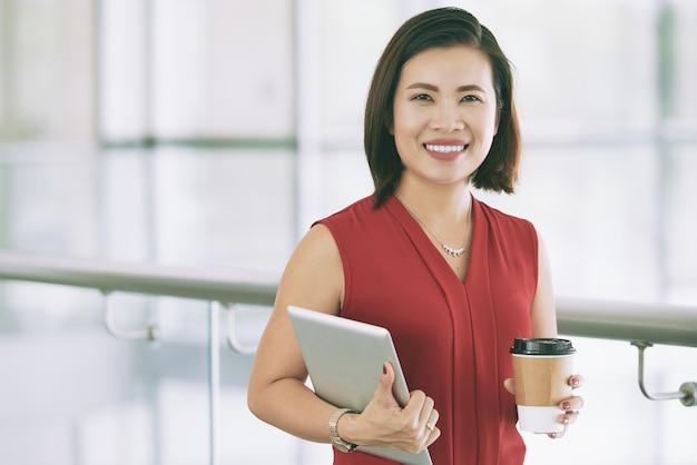 Uśmiechnięty azjatycki bizneswoman pozuje indoors na balkonie z pastylką i takeaway kawą