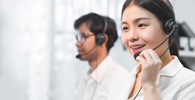 Uśmiechnięty azjatycki bizneswomanu konsultant jest ubranym mikrofon słuchawki obsługa klienta telefonu operator przy miejscem pracy.