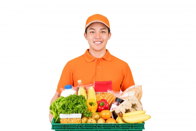 Uśmiechnięty azjatycki doręczeniowy mężczyzna w pomarańcze munduru mienia sklepu spożywczego koszu odizolowywającym