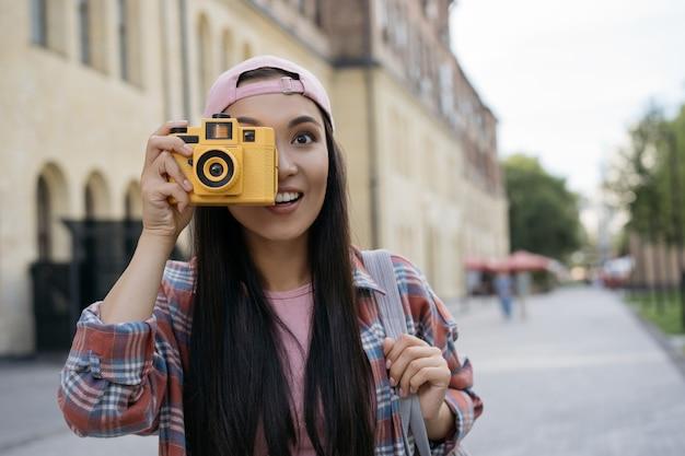 Uśmiechnięty azjatycki fotograf turystyczny robiący zdjęcia w plenerze