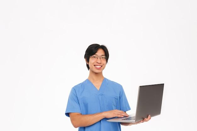 Uśmiechnięty azjatycki lekarz człowiek ubrany w mundur na białym tle nad białą ścianą, za pomocą komputera przenośnego
