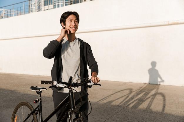 Uśmiechnięty azjatycki mężczyzna jadący na rowerze na zewnątrz, rozmawiający przez telefon komórkowy