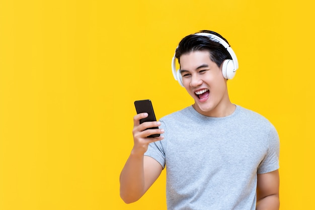 Uśmiechnięty azjatycki mężczyzna jest ubranym hełmofony słucha muzyka od smartphone