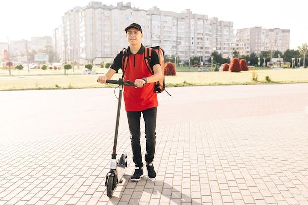 Uśmiechnięty azjatycki mężczyzna kurier dostarczający jedzenie z czerwonym plecakiem termicznym idzie ulicą ze skuterem elektrycznym