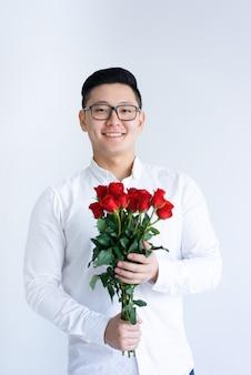Uśmiechnięty azjatycki mężczyzna trzyma wiązkę róże