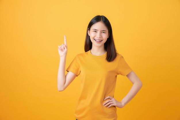 Uśmiechnięty azjatycki nastolatka stojak i wskazywać palec na pomarańcze.
