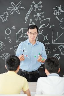 Uśmiechnięty azjatycki nauczyciel przedmiotów ścisłych, pokazujący ciekawym szkolnym molekularnym plastikowe modele