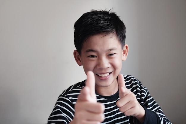 Uśmiechnięty azjatycki preteen nastoletni chłopak wskazuje palca pistoletu gest